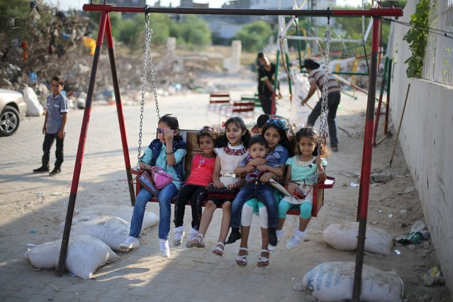 Palestinian children play on a swing near the ruins of houses, that witnesses said were destroyed by Israeli shelling during a 50-day war last summer, on the first day of Eid al-Fitr holiday, marking the end of the holy month of Ramadan, in the east of Gaza City, July 17, 2015. (Photo by Ibraheem Abu Mustafa/Reuters)