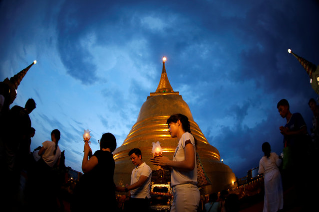 People walk around a stupa, at the top of the Wat Saket, or Golden Mount, during the Buddhist Vesak celebration in Bangkok, Thailand on May 10, 2017. (Photo by Jorge Silva/Reuters)