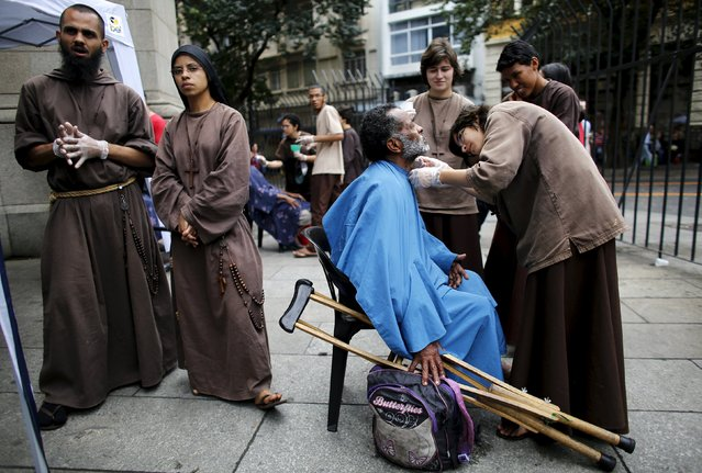 "Members of the Franciscan fraternity ""O Caminho"" (The Way), shave a homeless man in front of Se Cathedral in downtown Sao Paulo July 21, 2015. Sao Paulo, South America's largest city, has an estimated 16,000 homeless people according to the Town hall. ""O Caminho"" are a group of Franciscan monks and nuns who help the homeless. (Photo by Nacho Doce/Reuters)"