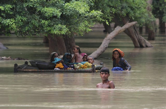 Pakistani villagers wade through floodwaters in Rajanpur, Pakistan, Pakistan, Thursday, July 23, 2015. (Photo by Asim Tanveer/AP Photo)