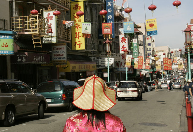 A woman looks at Chinese New Year banners hanging along a street in the Chinatown neighborhood of San Francisco, California February 5, 2007. (Photo by Robert Galbraith/Reuters)