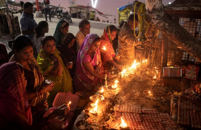 Hindu devotees light oil lamps at a temple after Supreme Court's verdict on a disputed religious site, in Ayodhya, India, November 9, 2019. (Photo by Danish Siddiqui/Reuters)