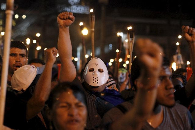 A demonstrator wears a mask as he gestures in a march to demand the resignation of Honduras' President Juan Orlando Hernandez in Tegucigalpa, July 24, 2015. Thousands of protesters have been continuing demonstrations in Tegucigalpa, calling for the resignation of Honduran President over a $200 million corruption scandal at the Honduran Institute of Social Security. (Photo by Jorge Cabrera/Reuters)