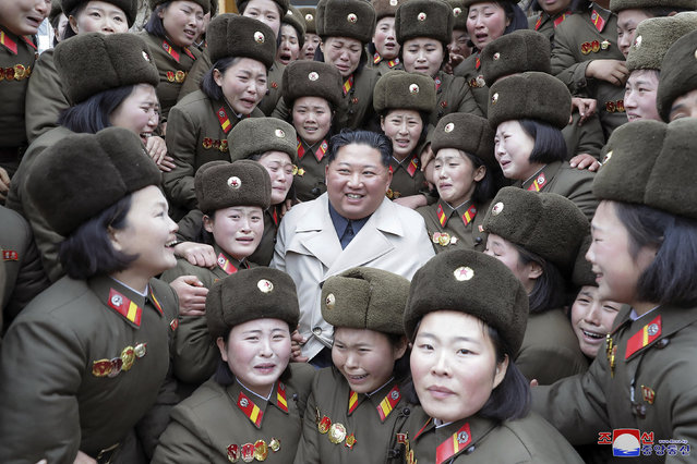 """In this undated photo provided on Monday, November 25, 2019, by the North Korean government, North Korean leader Kim Jong Un, center, poses as he inspects a women's company under Unit 5492 of the Korean People's Army in North Korea. Independent journalists were not given access to cover the event depicted in this image distributed by the North Korean government. The content of this image is as provided and cannot be independently verified. Korean language watermark on image as provided by source reads: """"KCNA"""" which is the abbreviation for Korean Central News Agency. (Photo by Korean Central News Agency/Korea News Service via AP Photo)"""
