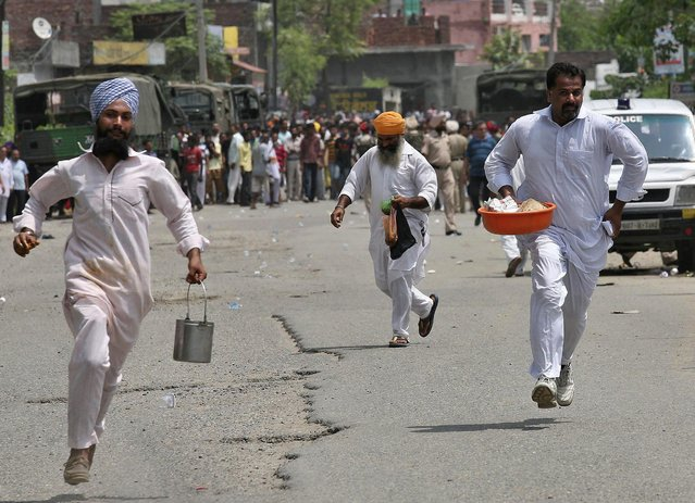 Local residents run near the site of a gunfight at a police station at Dinanagar town in Gurdaspur district of Punjab, India, July 27, 2015. (Photo by Munish Sharma/Reuters)