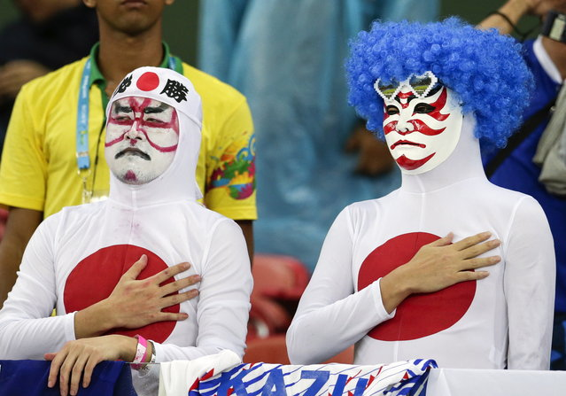 Japanese fans listen to their nation's national anthem before the group C World Cup soccer match between Ivory Coast and Japan at the Arena Pernambuco in Recife, Brazil, Saturday, June 14, 2014. (Photo by Petr David Josek/AP Photo)