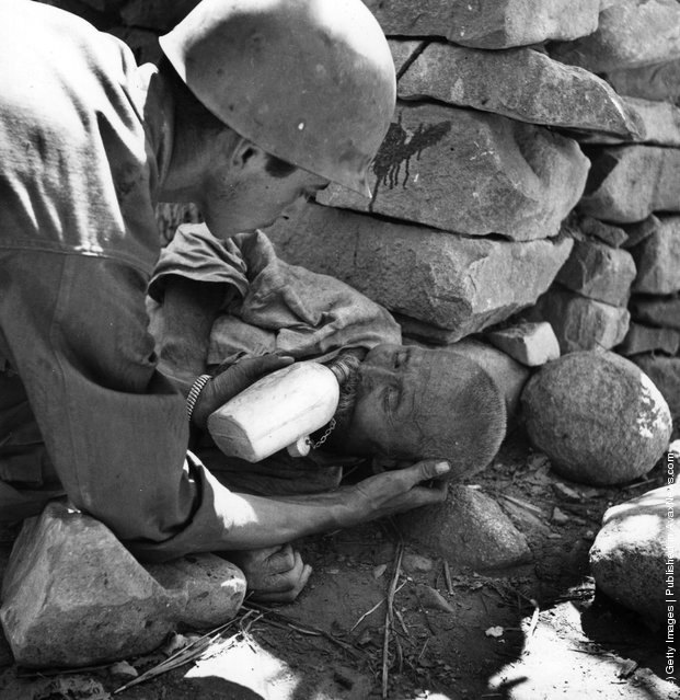 An American soldier helping a wounded Korean to drink, 1950