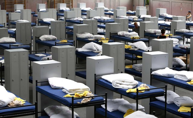 Workers arrange 200 beds and lockers in a sports hall of a school during preparations to receive asylum seekers, in Puchheim near Munich, July 29, 2015. (Photo by Michaela Rehle/Reuters)