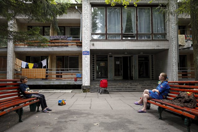 People sit on benches in the compound of a health and rest centre which serves as a temporary accommodation for refugees from eastern regions of the country in the town of Korostyshiv, Zhytomyr region, Ukraine, July 30, 2015. (Photo by Valentyn Ogirenko/Reuters)