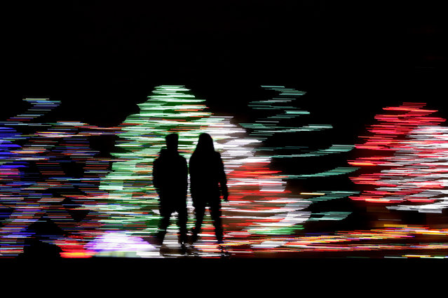 In this December 12, 2019 file photo taken with a long exposure, people are silhouetted against a Christmas display, at a park in Lenexa, Kan. Most Americans say the holiday season makes them feel very grateful and generous – but many report feeling stressed, too according to a new poll from The Associated Press-NORC Center for Public Affairs Research. (Photo by Charlie Riedel/AP Photo/File)