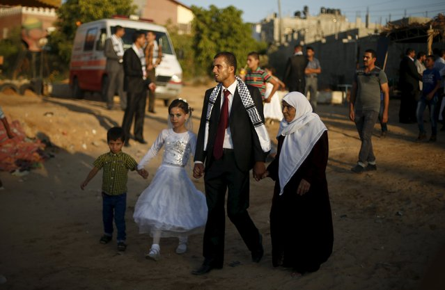 A Palestinian groom walks with his mother and siblings during a mass wedding for 150 couples in Beit Lahiya town in the northern Gaza Strip July 20, 2015. (Photo by Suhaib Salem/Reuters)