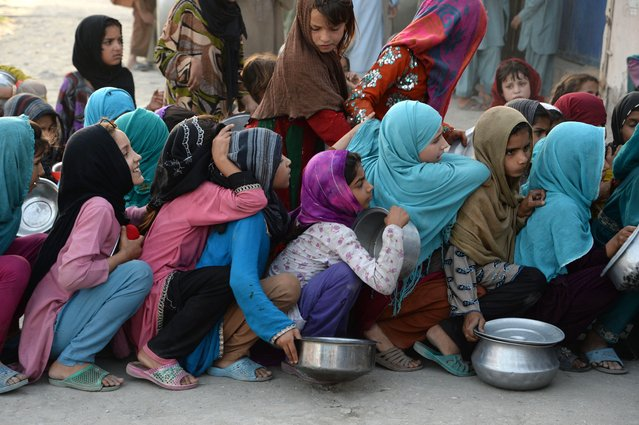 In this photograph taken on June 9, 2016, Afghan children hold dishes as they wait to receive food donated by a private charity for the needy during the Islamic holy month of Ramadan in the city of Jalalabad. Across the Muslim world, the faithful fast from dawn to dusk and strive to be more pious during the holy month, which ends with the Eid holiday. (Photo by Noorullah Shirzada/AFP Photo)