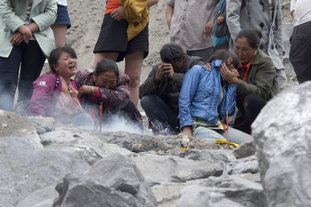 In this Sunday, June 25, 2017, file photo, family members grieve at the site of a landslide in Xinmo village in Maoxian County in southwestern China's Sichuan Province. Crews searching through the rubble left by a landslide that buried a mountain village under tons of soil and rocks in southwestern China found bodies, but many others remained missing. (AP Photo/Ng Han Guan, File)