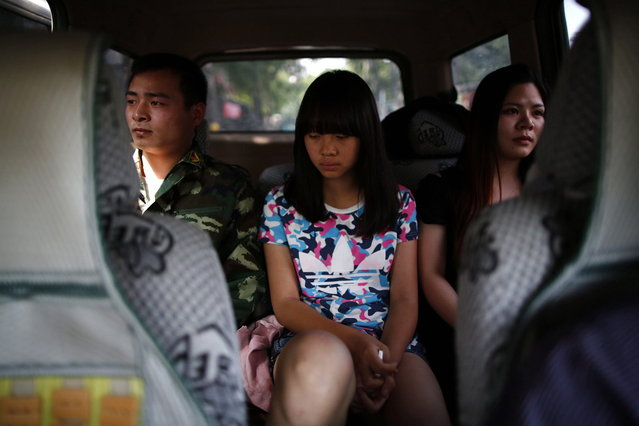 A female teacher and an instructor who is an ex-soldier, escort a girl in a car as they take her to the Qide Education Center at the request of her parents, in Beijing May 22, 2014. The Qide Education Center is a military-style boot camp which offers treatment for internet addiction. As growing numbers of young people in China immerse themselves in the cyber world, spending hours playing games online, worried parents are increasingly turning to boot camps to crush addiction. (Photo by Kim Kyung-Hoon/Reuters)