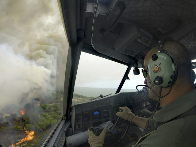 In this June 25, 2017 image made available by the Spanish Airforce on June 26, 2017, a Spanish firefighting plane flies over the fires in the Moguer area in southern Spain. A forest fire in southern Spain has forced the evacuation of 1,000 people and is threatening Donana National Park, one of Spain's most important nature reserves and a UNESCO World Heritage site since 1994, and famous for its biodiversity, authorities said Sunday. (Photo by Spanish Airforce via AP Photo)