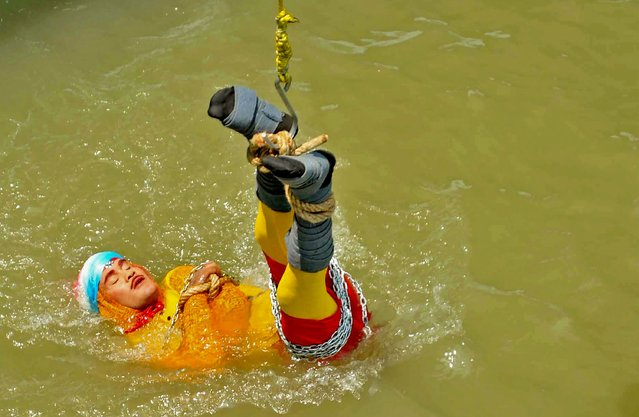 """In this photo taken on June 16, 2019 Indian stuntman Chanchal Lahiri, known by his stage name """"Jadugar Mandrake"""", is lowered into the Ganges river, while tied up with steel chains and ropes, in Kolkata. An Indian magician who went missing after being lowered into a river tied up in chains and ropes in a Houdini-inspired stunt is feared drowned, police said June 17. (Photo by AFP Photo/Stringer)"""