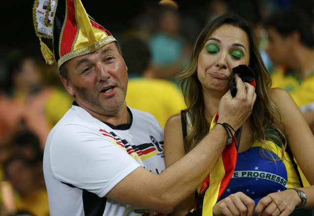 A Germany fan consoles a Brazil fan (R) during their 2014 World Cup semi-finals at the Mineirao stadium in Belo Horizonte July 8, 2014. (Photo by Damir Sagolj/Reuters)