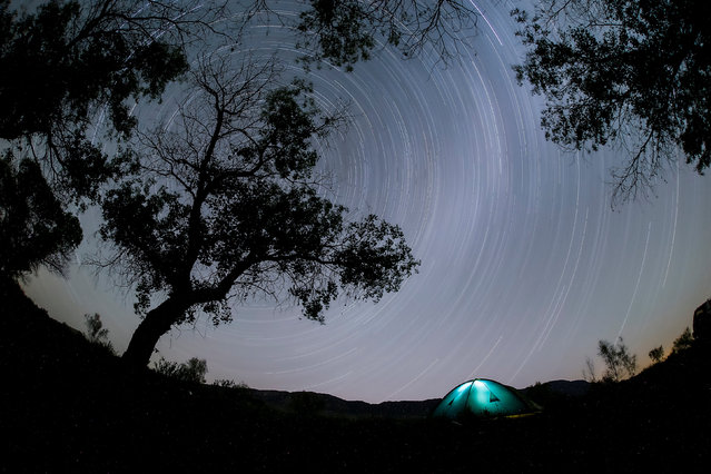 A long exposure photograph shows star trails in the night sky over a camp in Altyn-Emel national park, in Almaty region, Kazakhstan, May 13, 2016 (Photo by Shamil Zhumatov/Reuters)