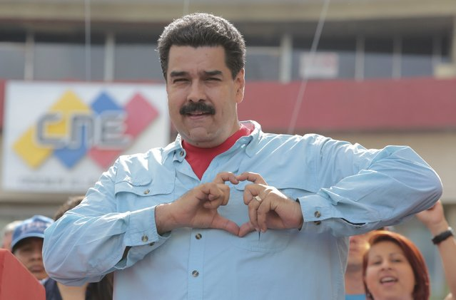 Venezuela's President Nicolas Maduro forms a heart shape with his hands during a rally with candidates of the electoral alliance Gran Polo Patriotico (Great Patriotic Pole), ahead of upcoming parliamentary elections, in Caracas, in this handout picture provided by Miraflores Palace on August 8, 2015. (Photo by Miraflores Palace/Reuters)
