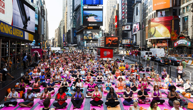 "People participate in a group yoga class in Times Square as part of the 14th annual ""Solstice in Times Square: Mind Over Madness Yoga"" to mark the summer solstice in New York, New York, USA, 20 June 2016. (Photo by Justin Lane/EPA)"