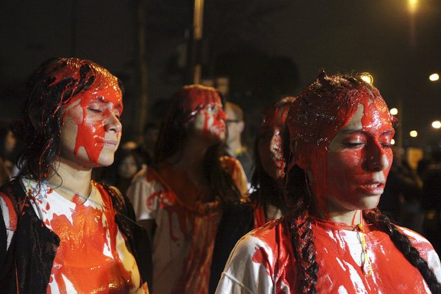Pro-abortion activists, covered with red paint, march towards the Congress to support a proposal to change Peruvian abortion laws in Lima, August 12, 2015. (Photo by Guadalupe Pardo/Reuters)