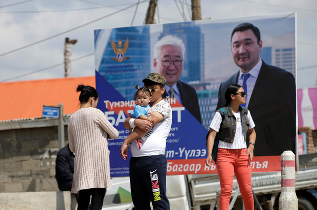 A father holds his daughter in front of a poster of candidates from Mongolian Democratic Party (MDP) on the outskirts of Ulan Bator, Mongolia, June 27, 2016. (Photo by Jason Lee/Reuters)