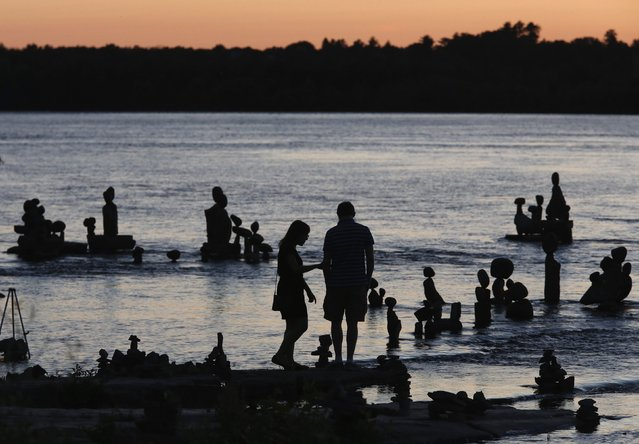 A couple look at stone sculptures at the Remic Rapids in the Ottawa River during sunset at Ottawa July 23, 2014. (Photo by Chris Wattie/Reuters)
