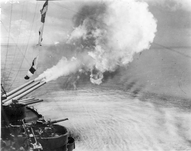 From Kiska to Kavieng, the old QUEEN has blasted the Japs. A class of battleship which is too slow to keep up with the latest fast Type of carriers is now a vital component of the most modrn, typed warefare, - amphibious ope rations, such as the taking and occupying of Guam, at which she is here shown firing. For the necessary close-in slugging and for her supporting call-fire, she cant be beat. And for the coordination and nerve to get in there and do it, the QUEEN'S CREW can't be beat either. We gripe because it's such a privilege it's become a habit. at one time, we called her The Virgin Queen. That was only a little over a long year ago. nobody so insults her now. And there would be some amphibious fun if we should overhear any ill-adives insinuations