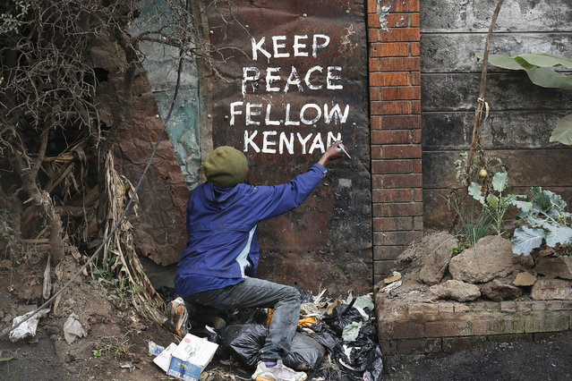Street artist Solomon Muyundo, also known as Solo7, paints a message of peace on the wall in Kibera slum, one of the opposition leader Raila Odinga's strongholds in the capital Nairobi, Kenya, 09 August 2017. Provisional result of the Presidential poll shows incumbent Uhuru Kenyatta leading Odinga who rejected them saying that the official tally doesn't match their own counts. The police is beefing up security on Nairobi streets as the fear of the post-election violence looms. (Photo by Dai Kurokawa/EPA)