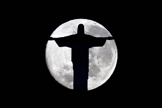A full moon rises behind the Christ the Redeemer statue in Rio de Janeiro, Brazil on July 4, 2012