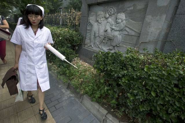Xin Ying, executive director to the Beijing LGBT Center which campaigns for gay rights walks past a relief sculpture depicting a family outside a court  where the first court case in China involving so-called conversion therapy is being held in Beijing, China, Thursday, July 31, 2014. (Photo by Ng Han Guan/AP Photo)