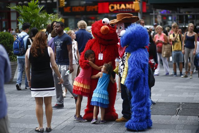 Jorge, an immigrant from Mexico, poses with children while dressed as the Sesame Street character Elmo in Times Square, New York July 30, 2014. (Photo by Eduardo Munoz/Reuters)