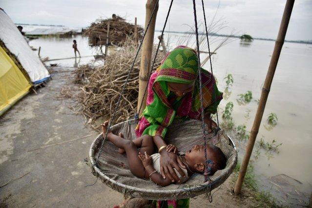 A mother comforts her son at a temporary shelter in the flood affected Morisutitop village, in the Morigaon district of north eastern Assam state, India on August 23, 2015. Seven people have died and over 650,000 people have been affected by floods in Assam. (Photo by Biju Boro/AFP Photo)