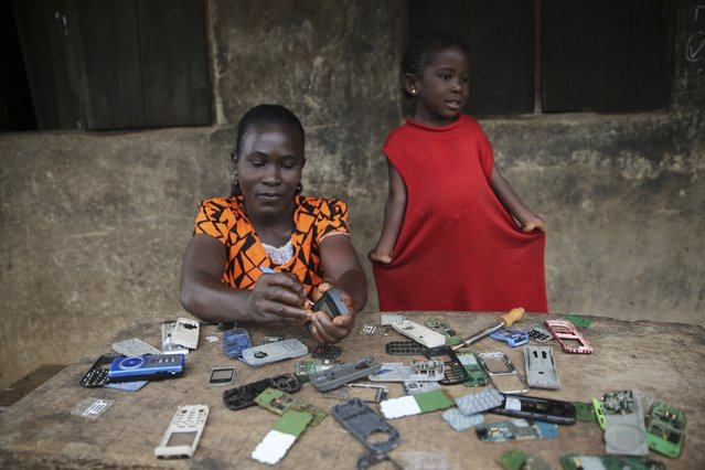 A woman repairs phones in front of a building during the Osun State governorship election at Ifofin village, Ilesa, southwest Nigeria August 9, 2014. (Photo by Akintunde Akinleye/Reuters)