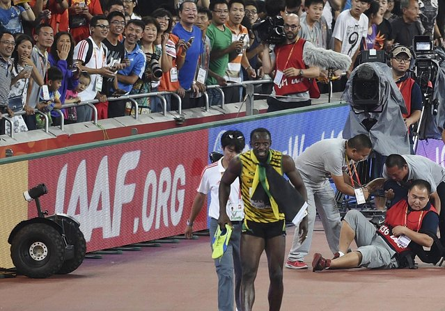 Usain Bolt of Jamaica (front R) limps after being knocked over by a cameraman (R) on a Segway after winning the men's 200 metres final at the 15th IAAF World Championships at the National Stadium in Beijing, China, August 27, 2015. (Photo by Reuters/Stringer)