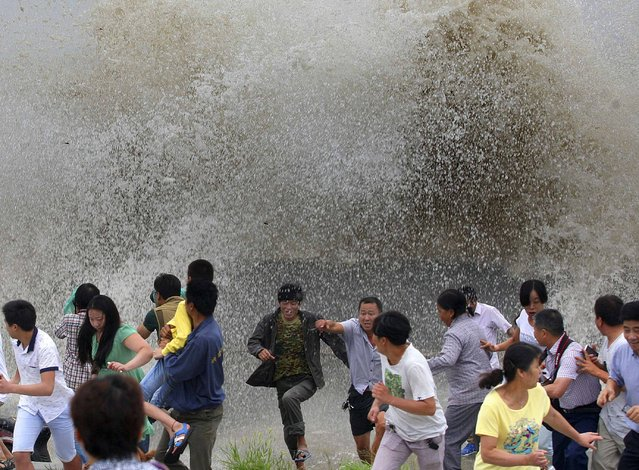 People run away from a tidal bore as it surges past a barrier on the banks of Qiantang River, in Hangzhou, Zhejiang province August 12, 2014. (Photo by Reuters/Stringer)