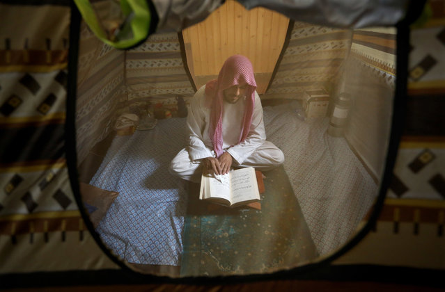 An Afghan Muslim man reads versus of the Quran in a mosque during Itikaf, the last ten days of the Islamic fasting month of Ramadan, in Kabul, Afghanistan, Wednesday, June 29, 2016. The last ten days of Ramadan, known as Itikaf, are very important according to many Muslims due to the belief that Prophet Muhammad used to exert himself even more in worship, hoping to draw himself closer to God. Itikaf involves total dedication to worship, reading Quran, and supplication. (Photo by Rahmat Gul/AP Photo)
