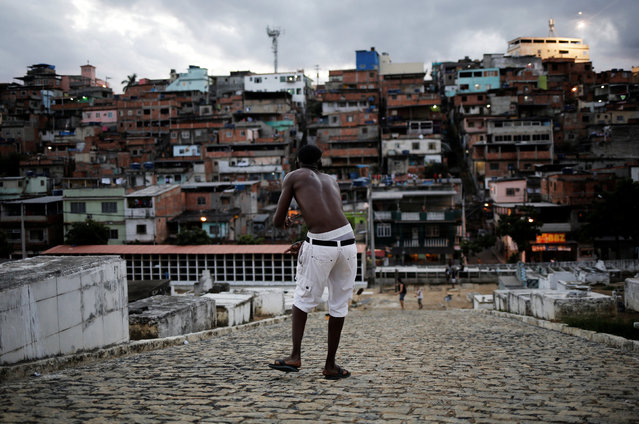 A man flies his kite in a cemetery in the Vila Operaria Favela of Rio de Janeiro, Brazil, June 26, 2016. (Photo by Nacho Doce/Reuters)
