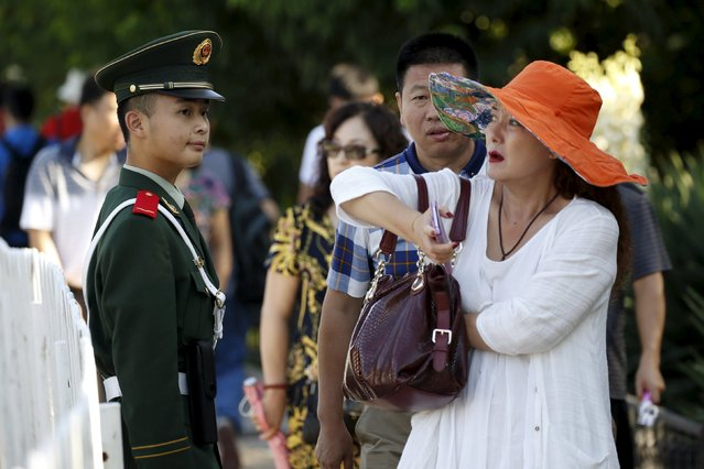 A woman walks past a paramilitary policeman near the Changan Avenue, ahead of the military parade to mark the 70th anniversary of the end of World War Two, in Beijing, China, September 3, 2015. (Photo by Kim Kyung-Hoon/Reuters)