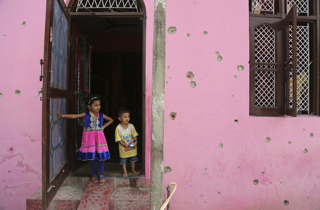 Indian children stand by the door to a house damaged by firing, allegedly from the Pakistan side of the border, near the International Border in Arnia village near, about 47 kilometers (30 miles) from Jammu, India, Friday, September 22, 2017. Schools in the international border area have been closed and residents are moving to safer areas as firing continued in the region. India and Pakistan have a long history of bitter relations over Kashmir. They have fought two of their three wars over the region since they gained independence from British colonial rule in 1947. (Photo by Channi Anand/AP Photo )