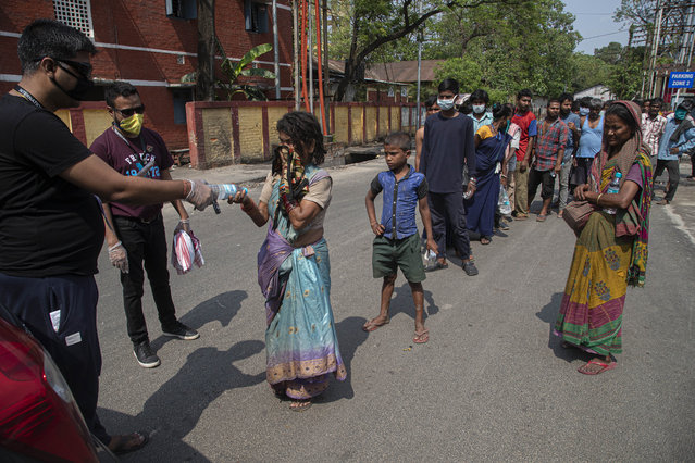 A group of Indians distribute free food and water to homeless people during a nationwide lockdown to curb the spread of new coronavirus in Gauhati, India, Sunday, April 19, 2020. (Photo by Anupam Nath/AP Photo)