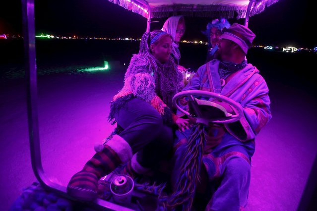 "Participants (L-R) Amanda McPhail, Erika Minaberry, Thomas Young and Dennis Somerhalder make their across the Playa in a modified golf cart during the Burning Man 2015 ""Carnival of Mirrors"" arts and music festival in the Black Rock Desert of Nevada, September 3, 2015. (Photo by Jim Urquhart/Reuters)"