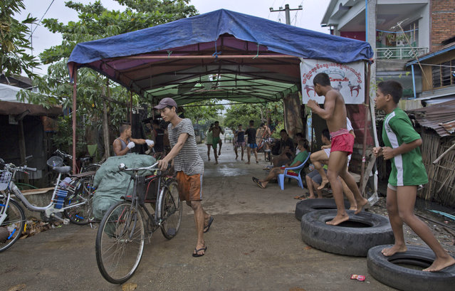 In this Tuesday, July 14, 2015, photo, members of the White New Blood lethwei fighters club, a Myanmar traditional martial-arts club which practices a rough form of kickboxing, warm up in their gym on a street as a man pushes his rickshaw with a load of charcoal in Oakalarpa, north of Yangon, Myanmar. (Photo by Gemunu Amarasinghe/AP Photo)