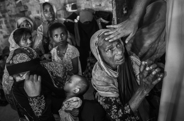 A cleric touches the head of a Rohingya refugee woman as she asks for food as they rest in an Islamic school or madrassa  after arriving by boat on the Bangladesh side of the Naf River at Shah Porir Dwip after fleeing their villages in Myanmar, on September 22, 2017 in Cox's Bazar, Bangladesh. (Photo by Kevin Frayer/Getty Images)