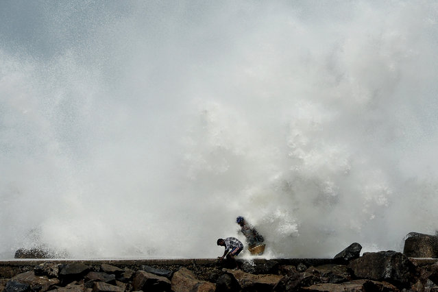 Men walk past as waves hit a breakwater at Kasimedu fishing harbour in Chennai on May 19, 2020, as Cyclone Amphan barrels towards India's eastern coast. Millions of people were being moved to safety on May 19 as one of the fiercest cyclones in decades barrelled towards India and Bangladesh, with evacuation plans complicated by coronavirus precautions. Both countries are under various stages of lockdown because of the disease, with infections still surging. (Photo by Arun Sankar/AFP Photo)