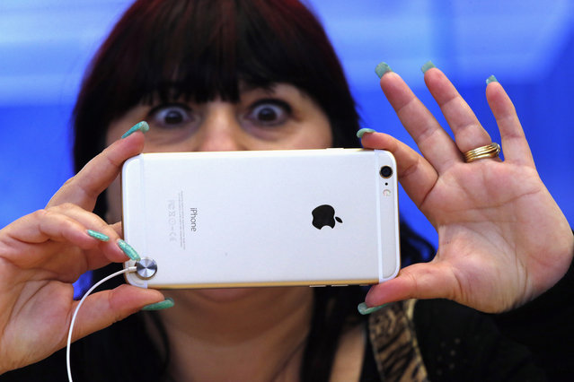 A woman reacts as she takes a photograph on an iPhone 6 Plus after it went on sale at the Apple store in Sydney September 19, 2014. Hundreds of customers waited in lines outside the store on the first day the new iPhone became available. (Photo by David Gray/Reuters)