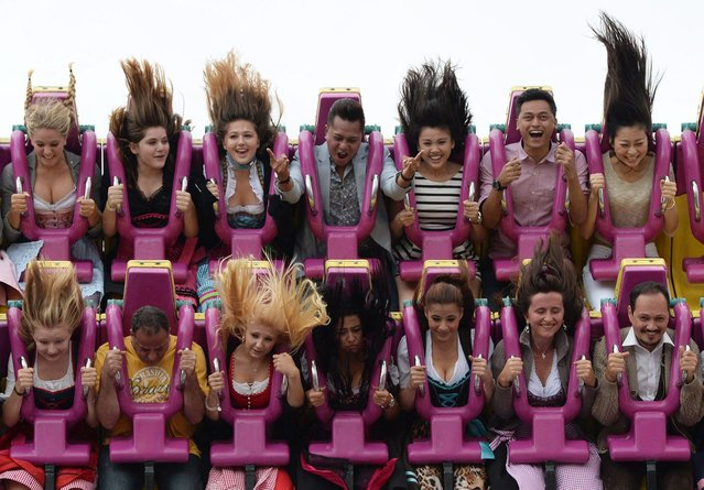 Visitors enjoy a fun ride on the opening day of the traditional Bavarian Oktoberfest festival at the Theresienwiese fair grounds in Munich, southern Germany, on September 20, 2014. (Photo by Christof Stache/AFP Photo)