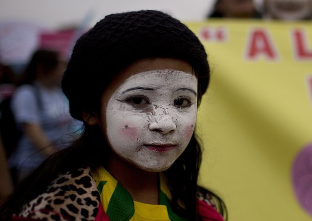 A girl takes part in a march against domestic violence in Lima, Peru, Saturday, August 13, 2016. (Photo by Rodrigo Abd/AP Photo)
