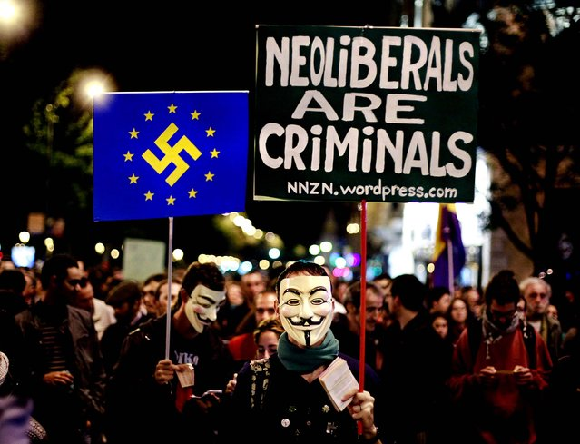 """Protesters hold banners, one reading """"Neoliberals are criminals"""" and another with an EU flag with the Nazi symbol on it during a demonstration outside Parliament as lawmakers debate budget spending cuts for 2013 in Madrid, Spain October 23, 2012. (Photo by Andres Kudacki/Associated Press)"""