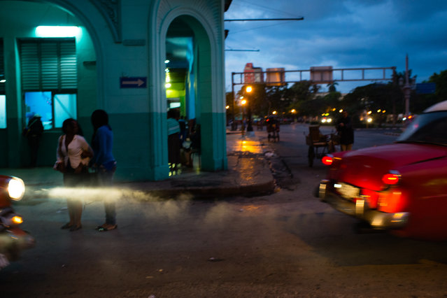 As the sun rises over Old Havana on January 31, 2015, cars drive by polluting the air as pedestrians make their way to work. (Photo by Sarah L. Voisin/The Washington Post)